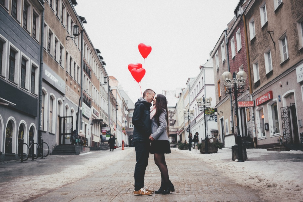 Two people standing on road kissing with balloons above them