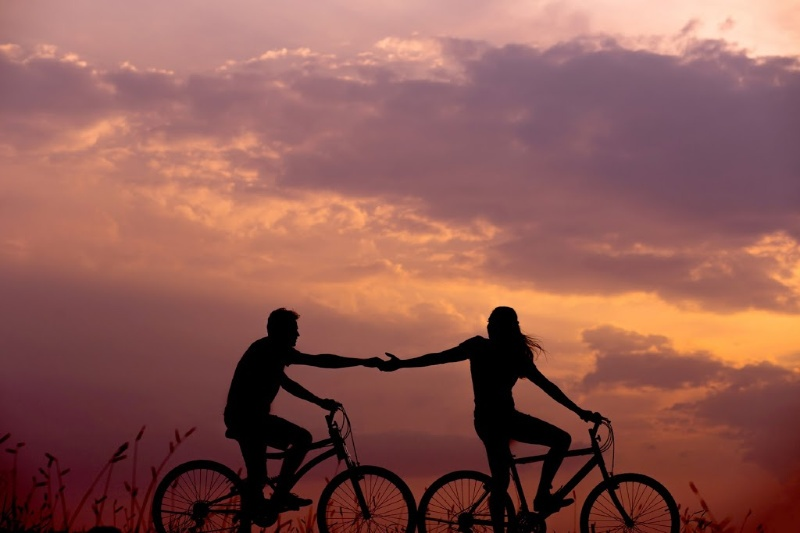 Two people riding bikes as sunsets, reaching for each others hands