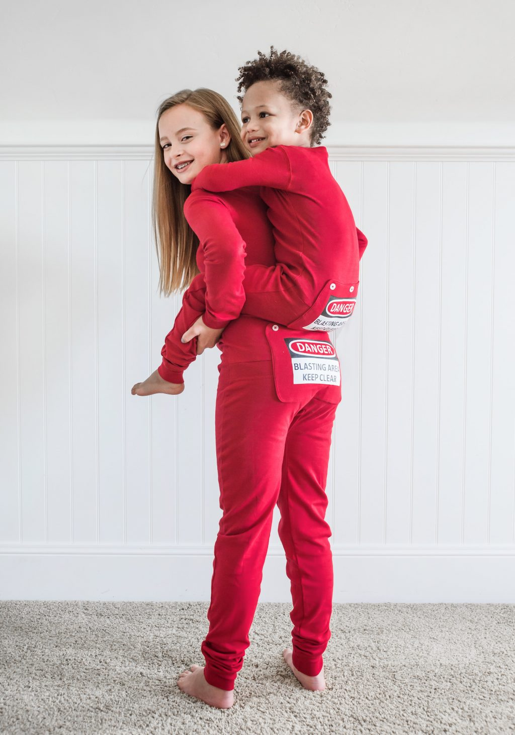Super soft and warm stretchable rib knit cotton union suit onesie pajamas for boys and girls in youth sizes 4 through 14. For superior comfort these pajamas have flat stitching and tag-free labels. This red one piece pajama, in the classical union suit design, has red snaps for front closure and features a non-functioning 3 button dropseat butt flap that has a printed warning sign that reads: DANGER - BLASTING AREA - KEEP CLEAR. Matching onesie available for adults.