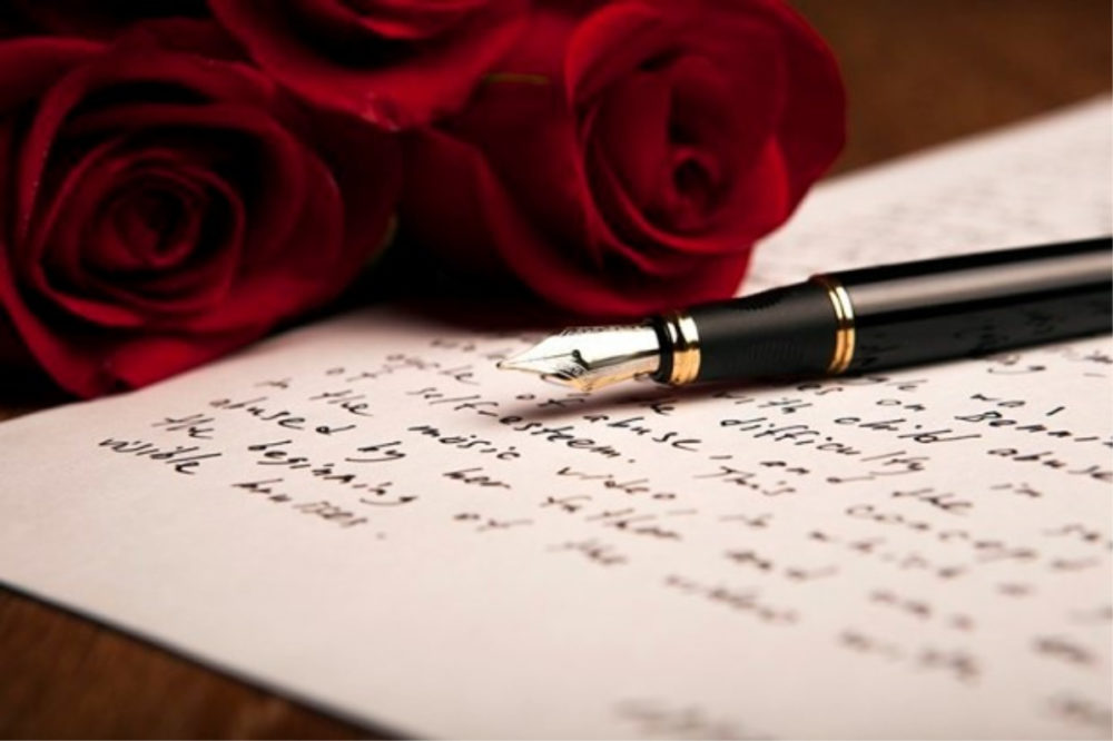 red rose sitting on a note besides a pen