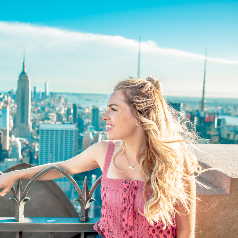 woman on top of tower and overlooking Empire State Building