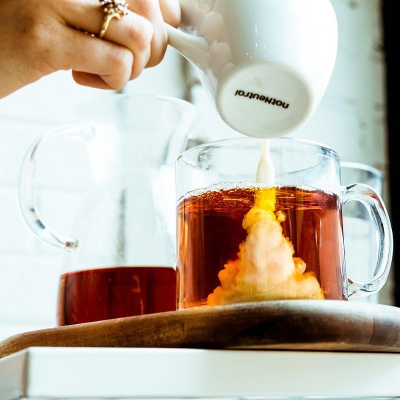 person pouring Coffee Creamer into mug