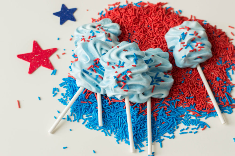 Patriotic Meringue Pops sitting on sprinkles