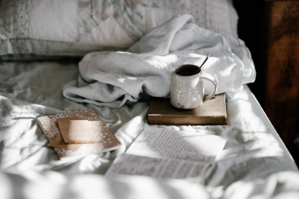 cup and book on bed