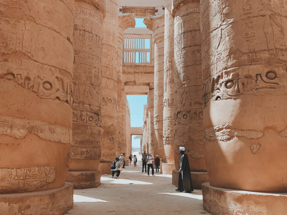 people standing near Egypt pillars
