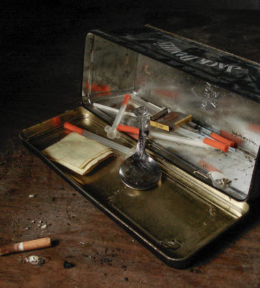 spoon and syringes inside metal box