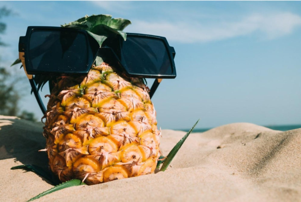 pineapple sitting on sand with sun glasses on
