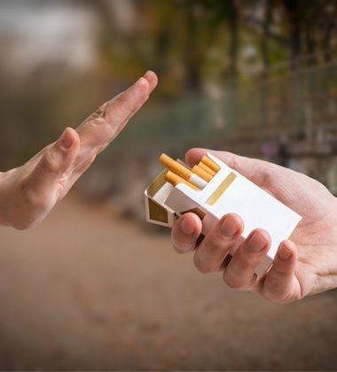 hand waving away cigarette pack