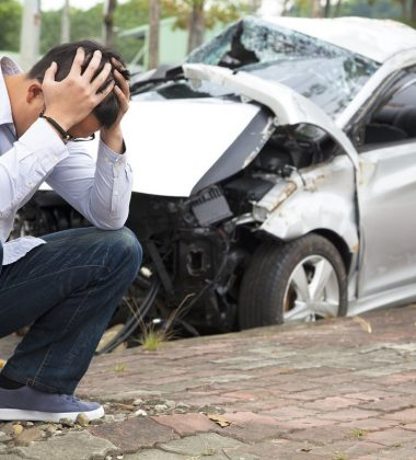 car accident and person kneeling holding head