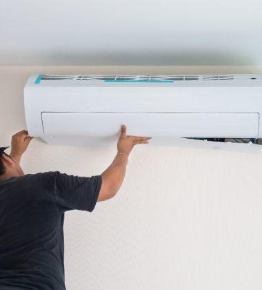 man putting up AC unit
