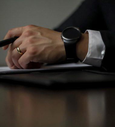 hands on desk, holding pen