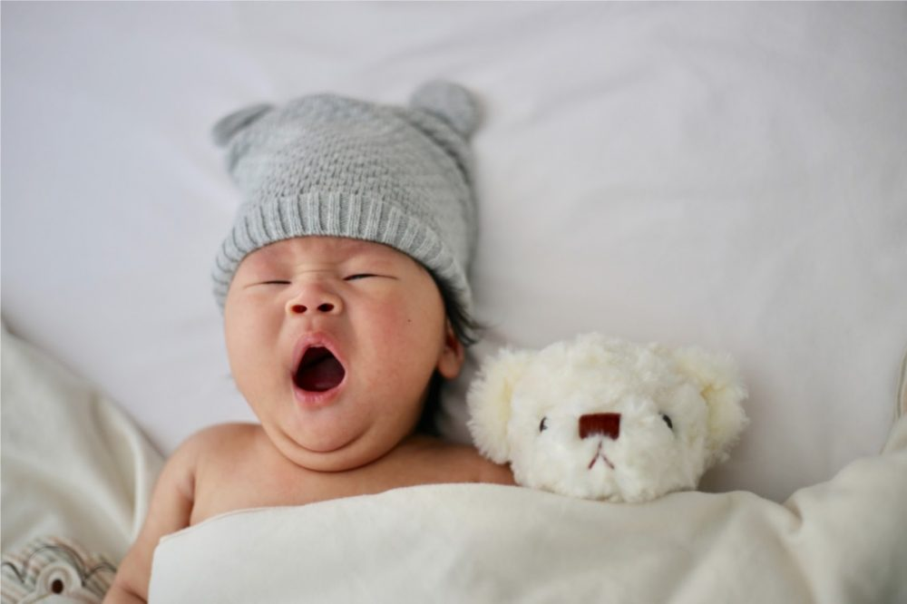 baby laying in back yawning with a stuffed animal next to him