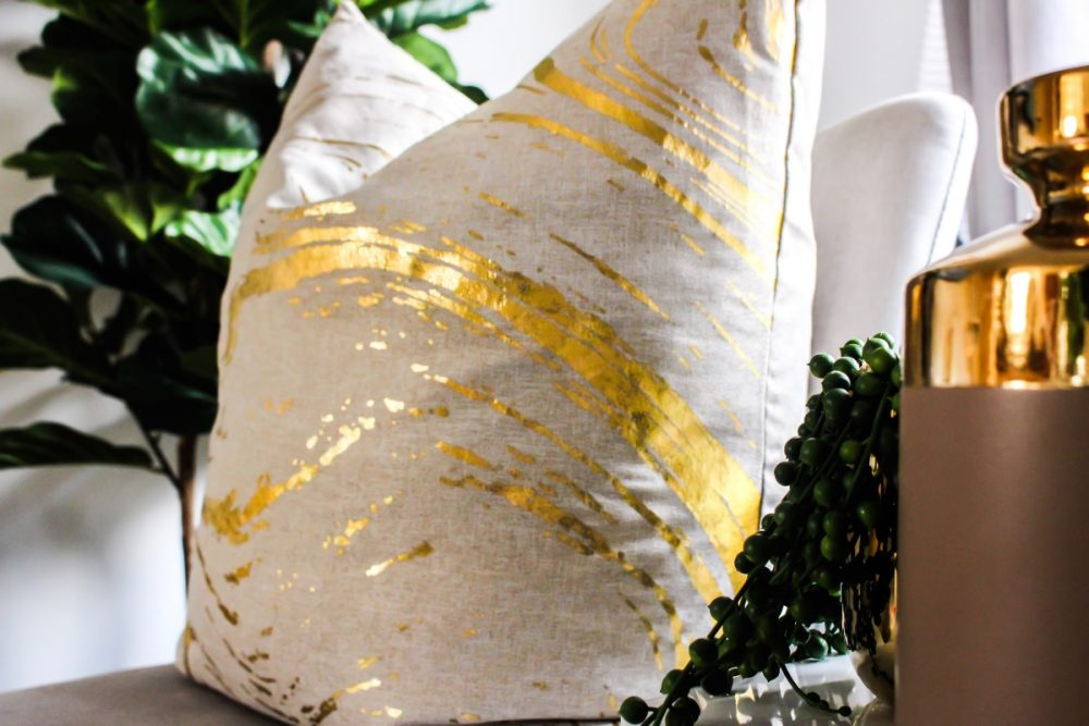 white pillow with gold stripe