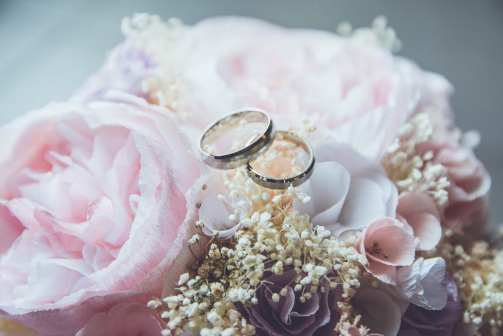 gold-colored bridal ring set on pink rose flower bouquet