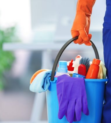 person holding blue bucket with cleaning supplies