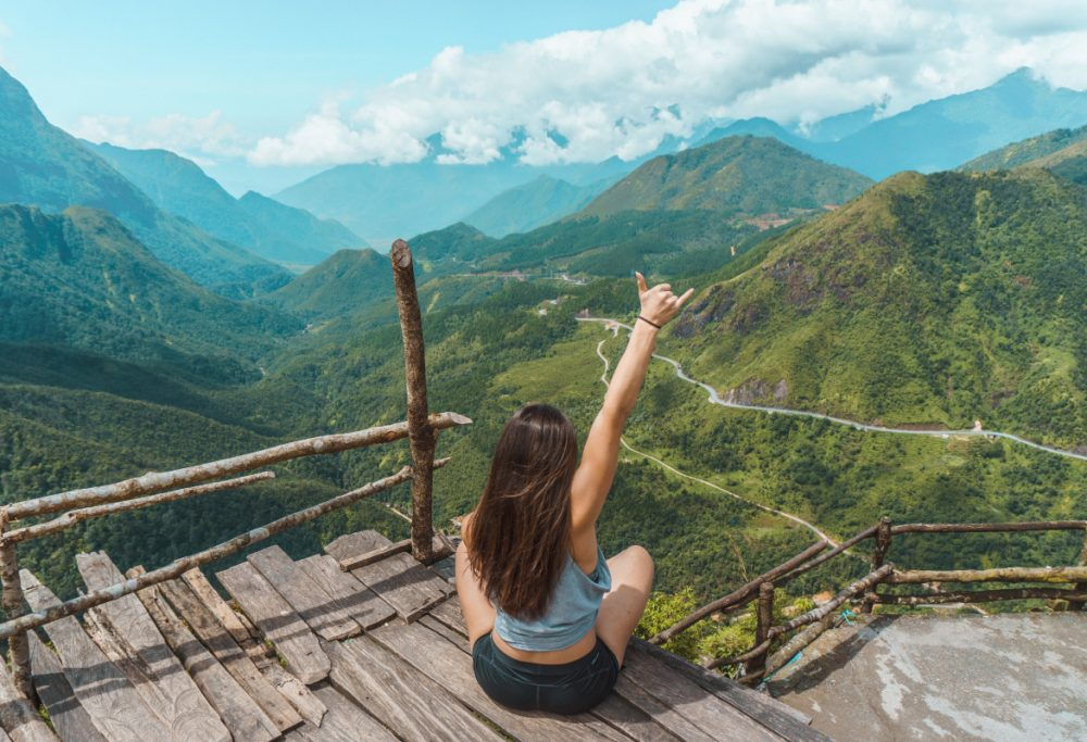 woman raising hand on mountain top
