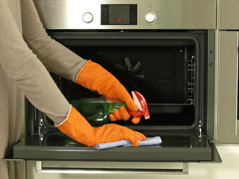 person cleaning oven