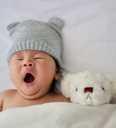 baby with blue hat on yawning