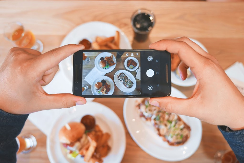 person taking picture of food