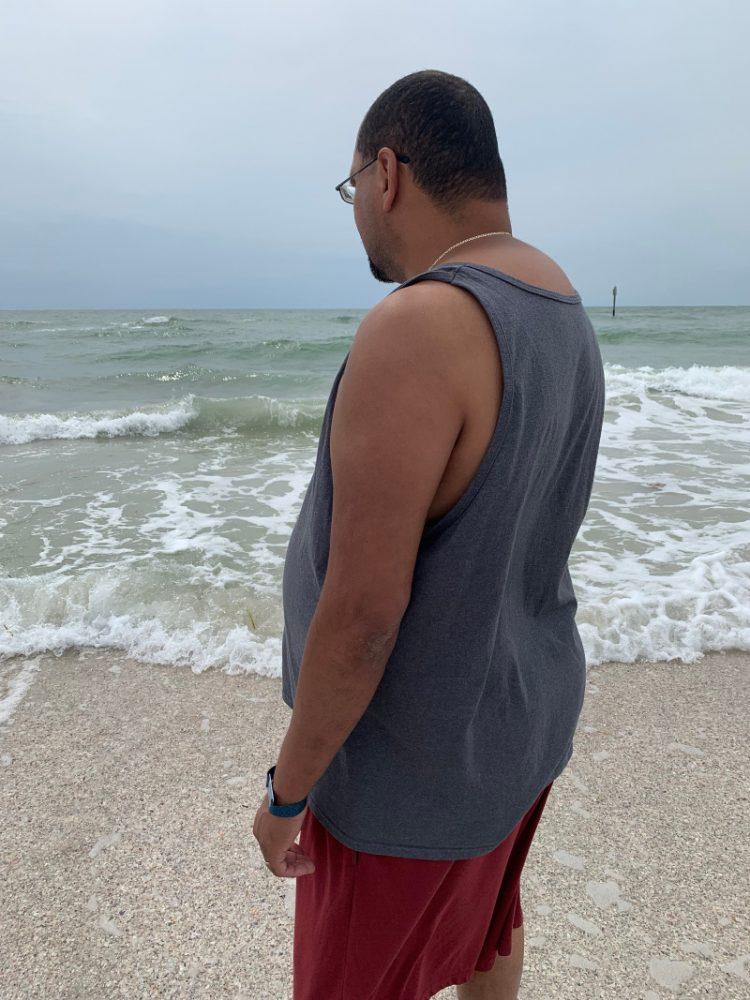 man on beach watching water
