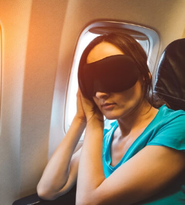 Young woman sleeping on a plane with black eye mask on her face - tired girl resting during a long flight - jet lag concept