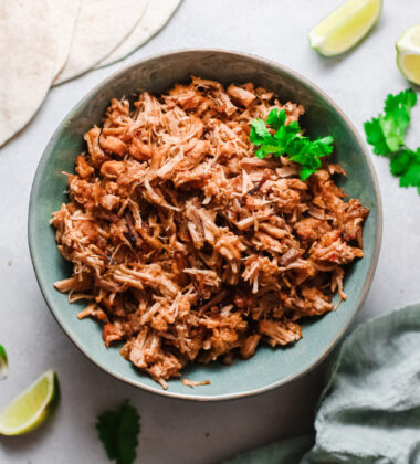 Instant Pot Mexican Carnitas in a blue bowl with tortillas