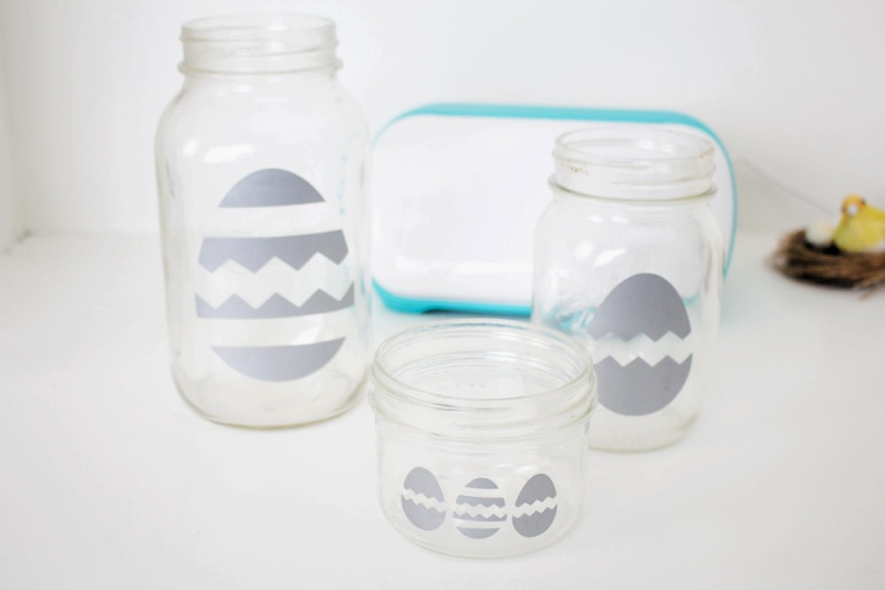 three glass jars with eggs on them